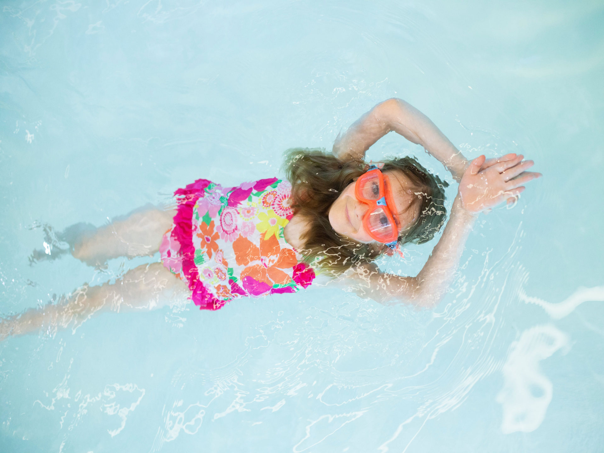 Young girl swim on her back