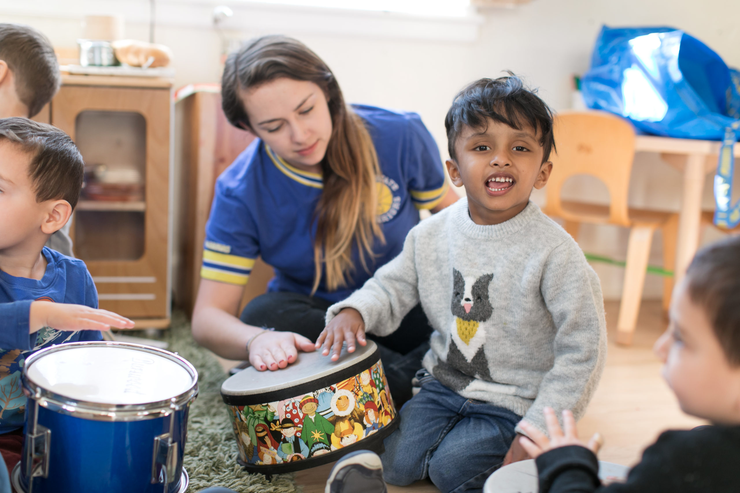 Boy and teacher play with drum