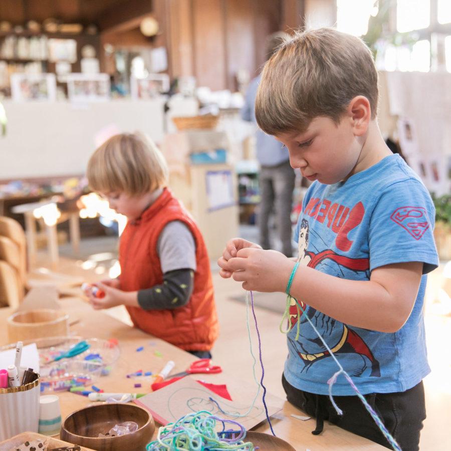Two preschool boys working with yarn