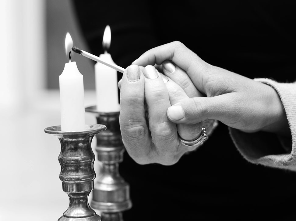 People lighting Shabbat candles