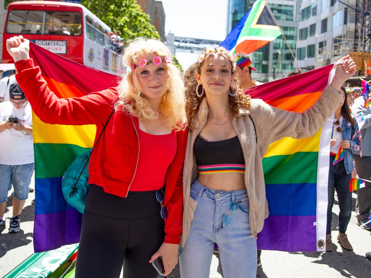 Two women holding Pride flag