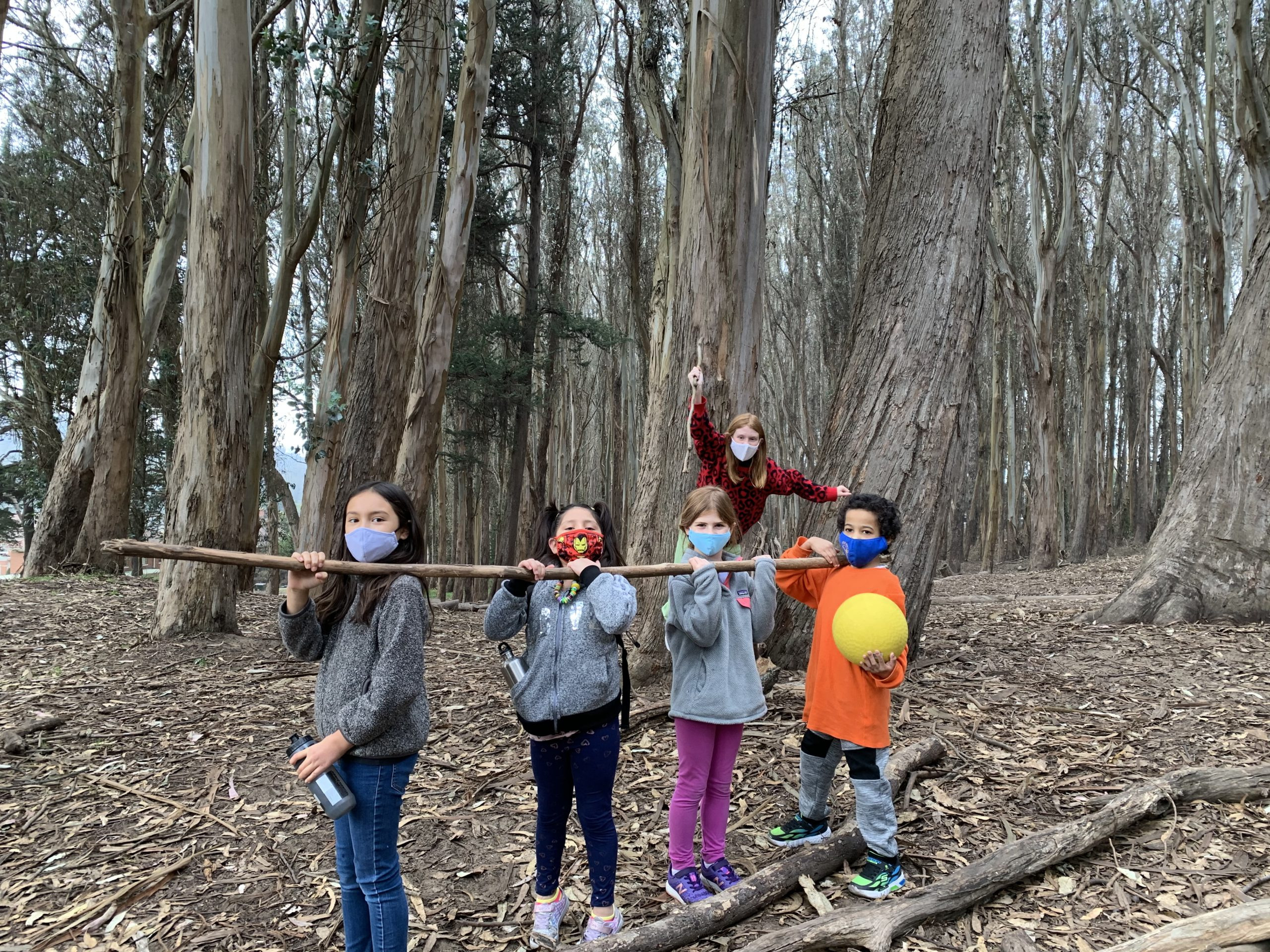 Children in the woods holding a stick