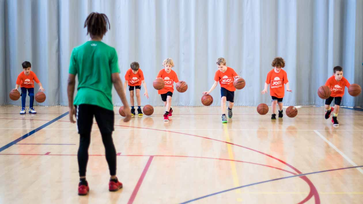 Youth basketball group lines up to practice dribbling