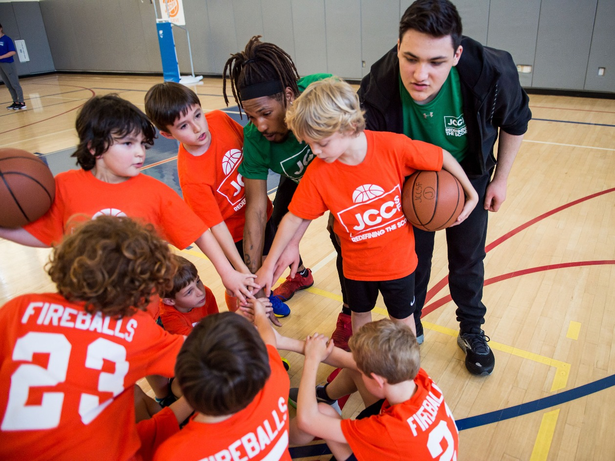 Basketball players and coaches in a huddle
