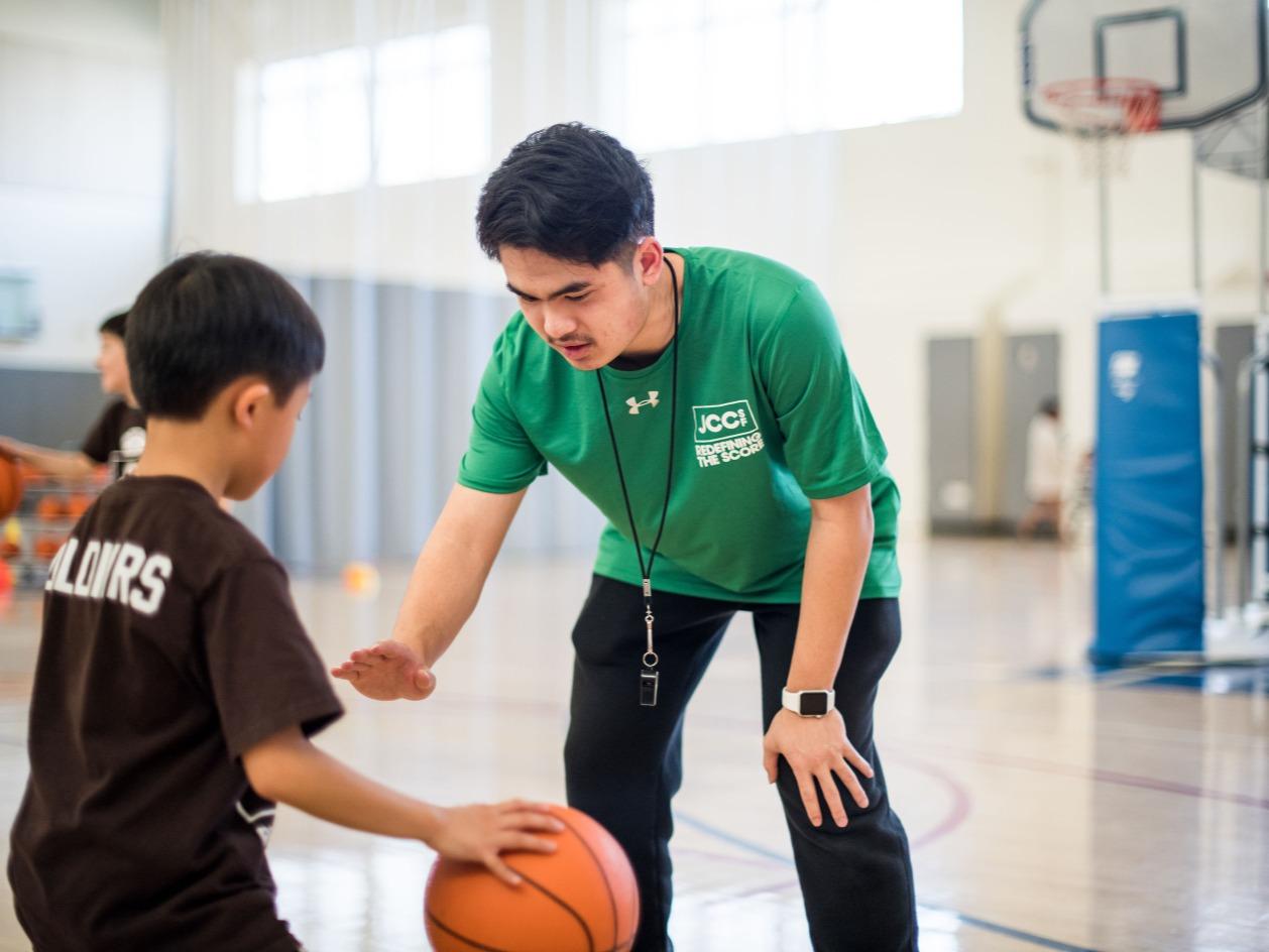 Basketball coach teaches a boy to dribble