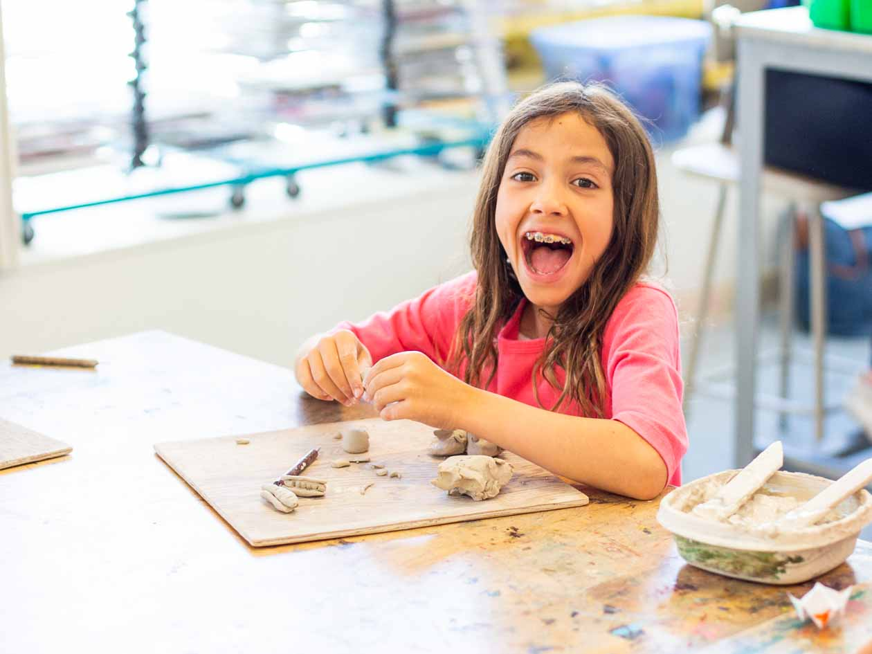 Girl looks excitedly at camera while working with clay