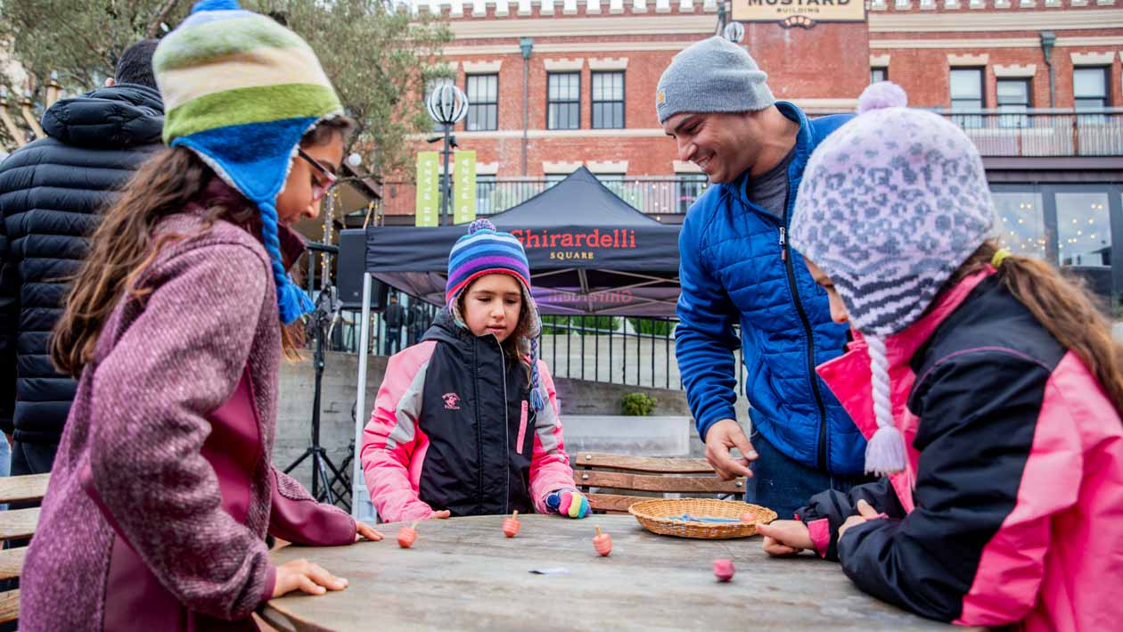 Man and children play game at Ghirardelli popup