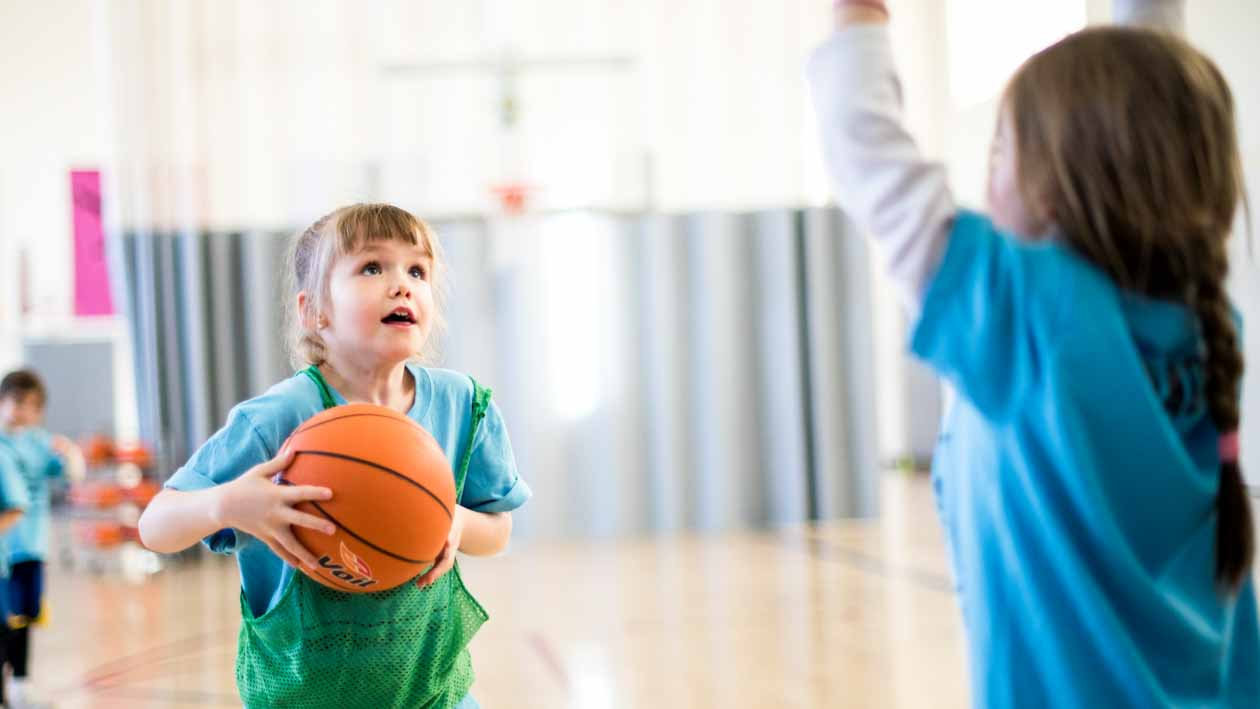 Girl shoots basketball during youth practice