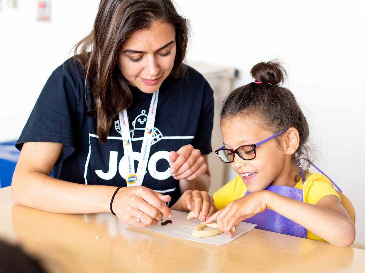 JCCSF instructor helps young girl make challah
