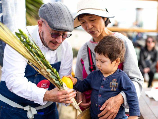 Merchant shows veggies to young boy