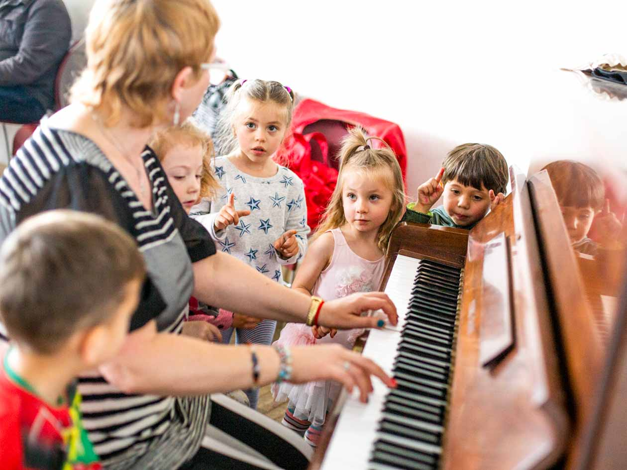 Older woman plays piano for children's music class