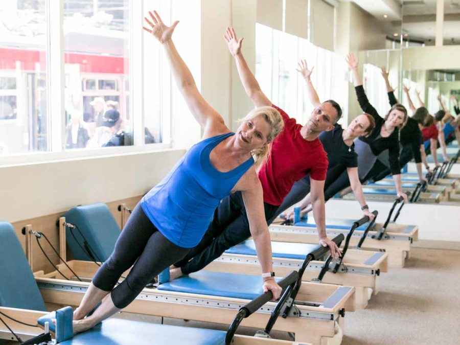 Pilates group poses on reformers