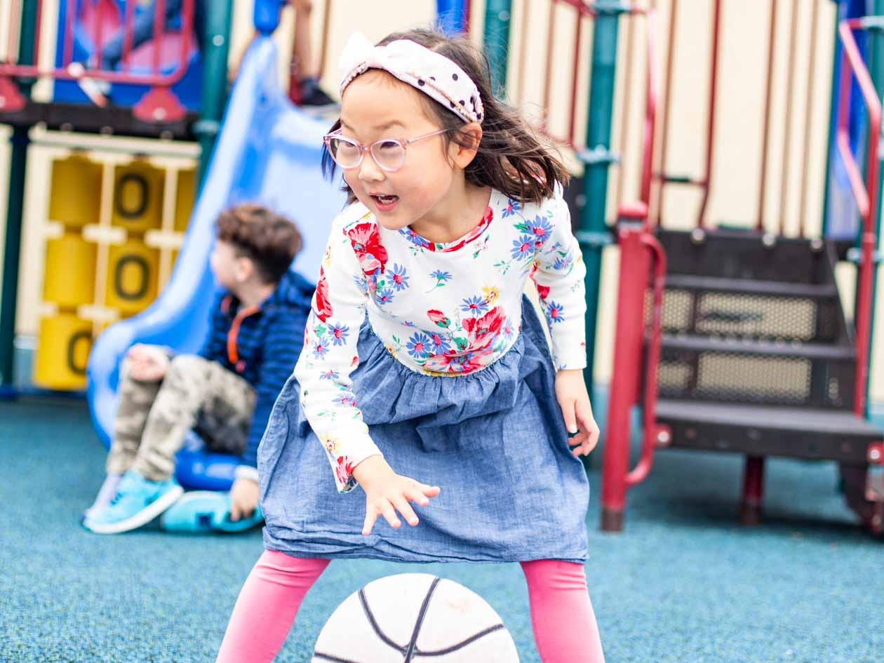 Preschool girl dribbles basketball on playground