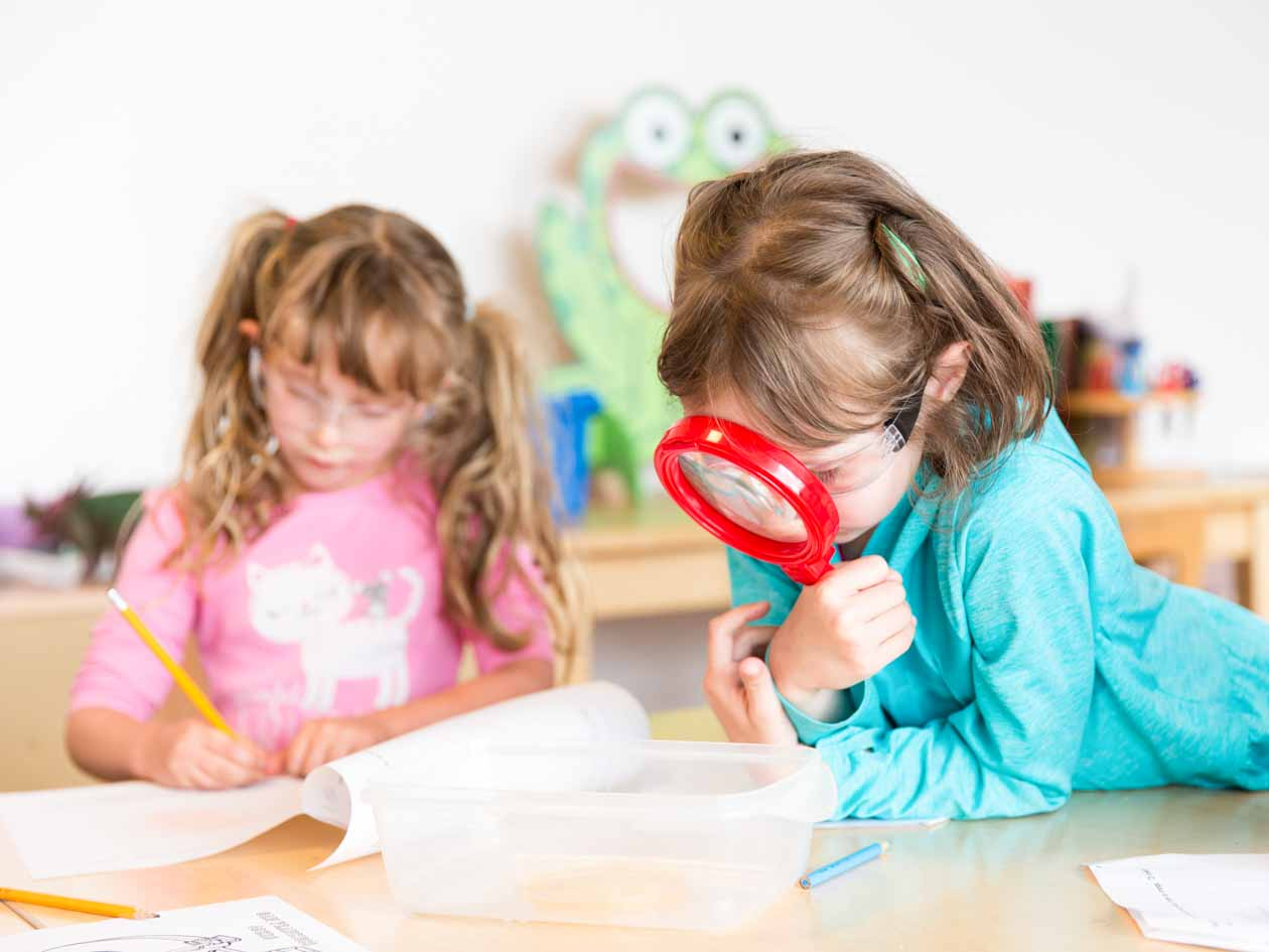 Preschool girl uses large red magnifying glass