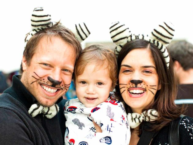 Parents with cat whisker face paint hold young child during Purim celebration