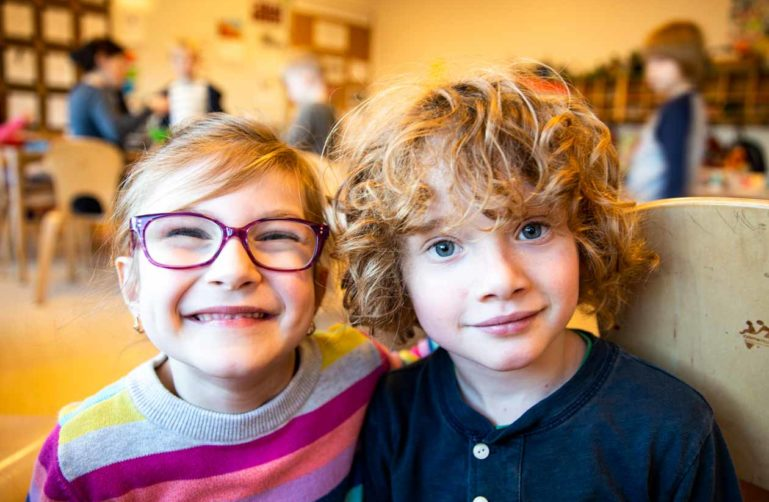 Two preschoolers smile at camera