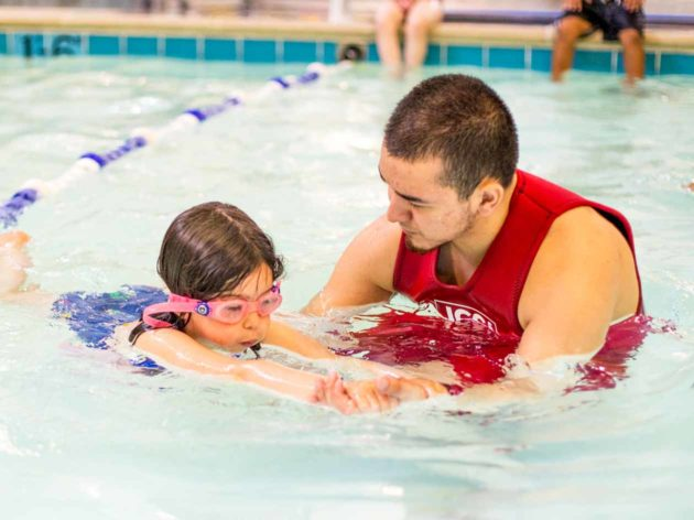 Swim instructor teaches young girl in pool