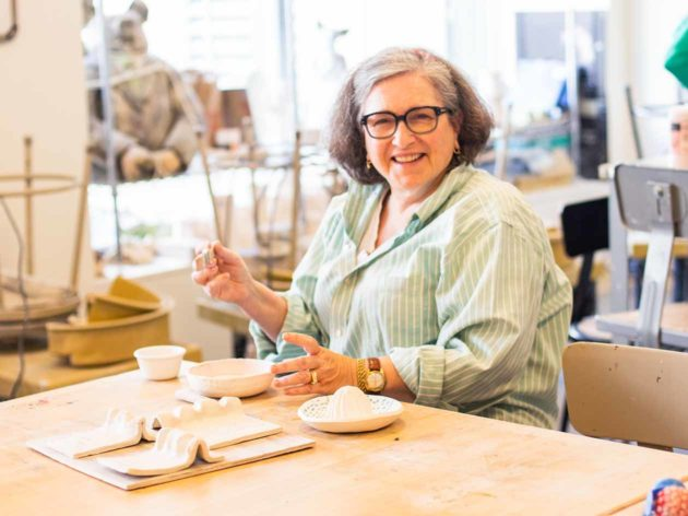 Older adult woman works on ceramic class project