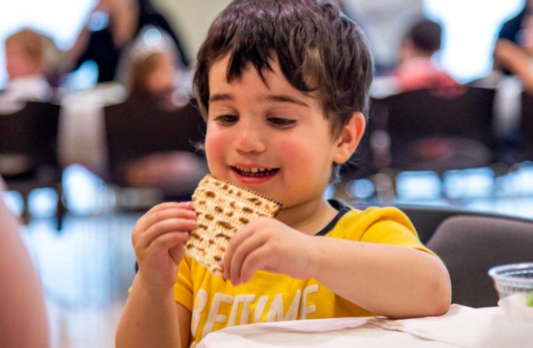 Young boy eats bread at Passover gathering