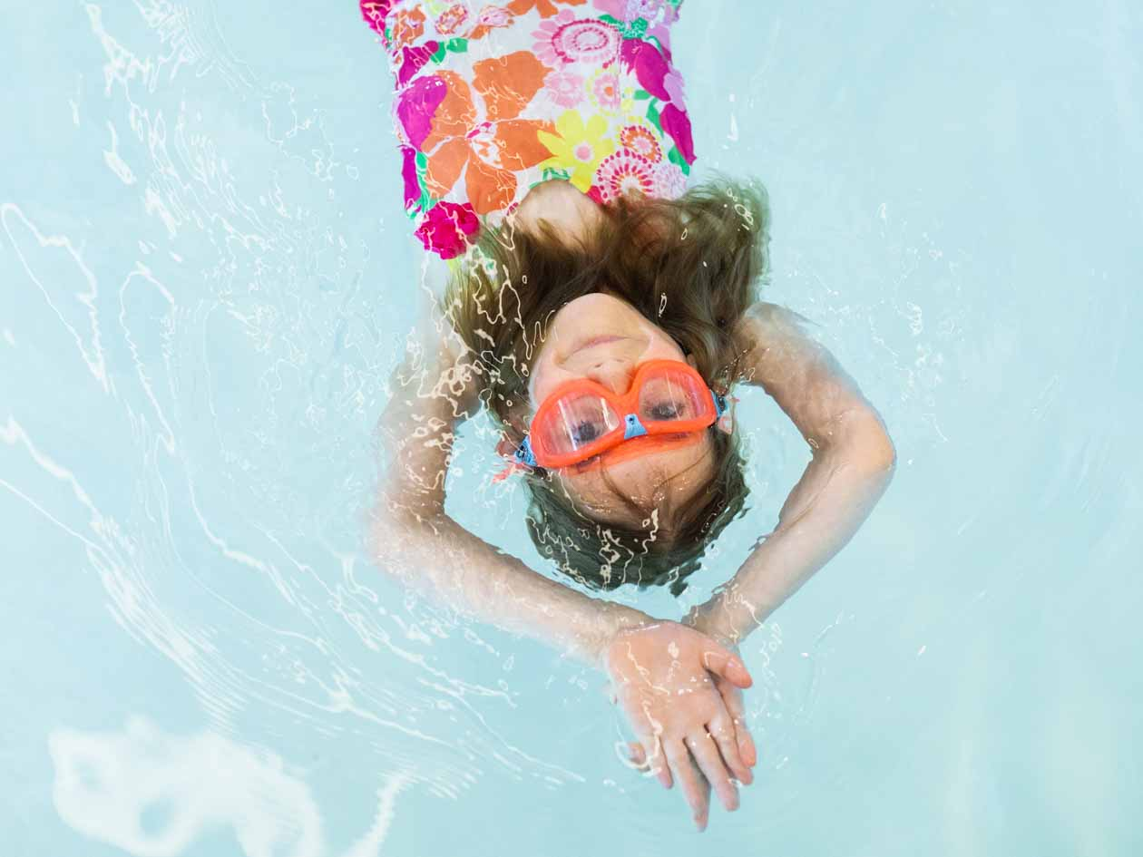Young girl does backstroke in pool