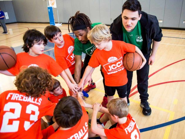 Youth basketball group circles up with hands in