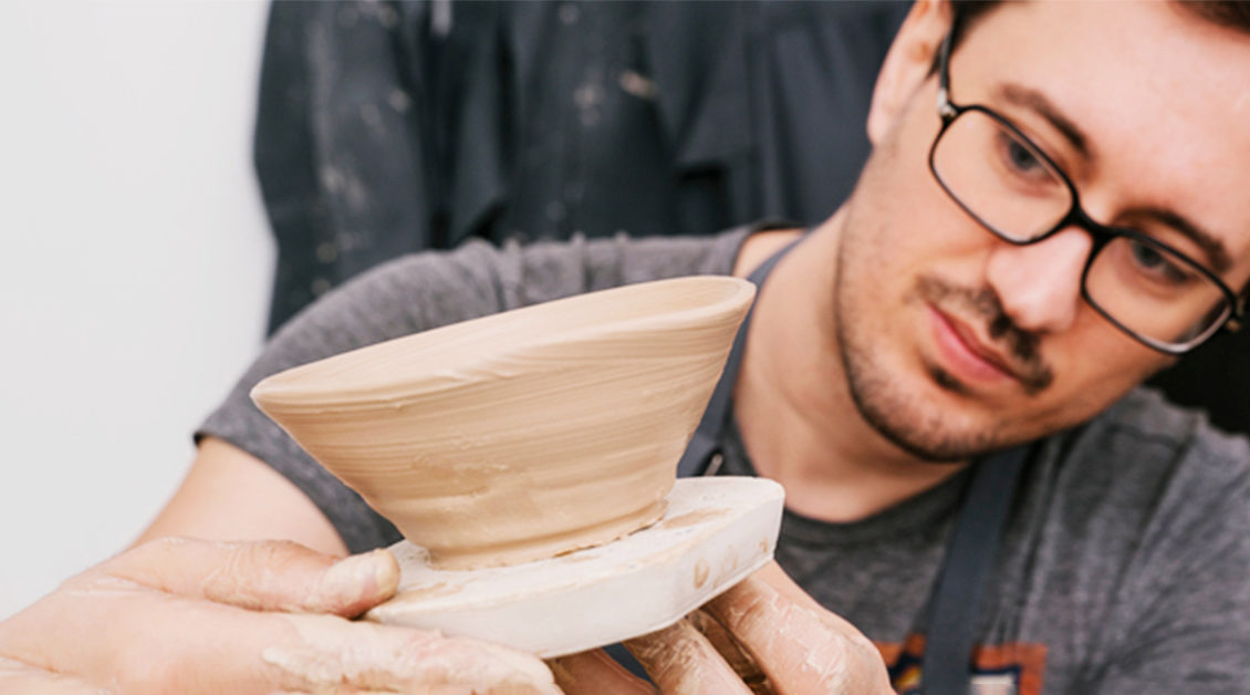 man looking at clay pot