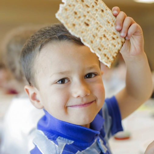 Young boy holding up a piece of matzo bread