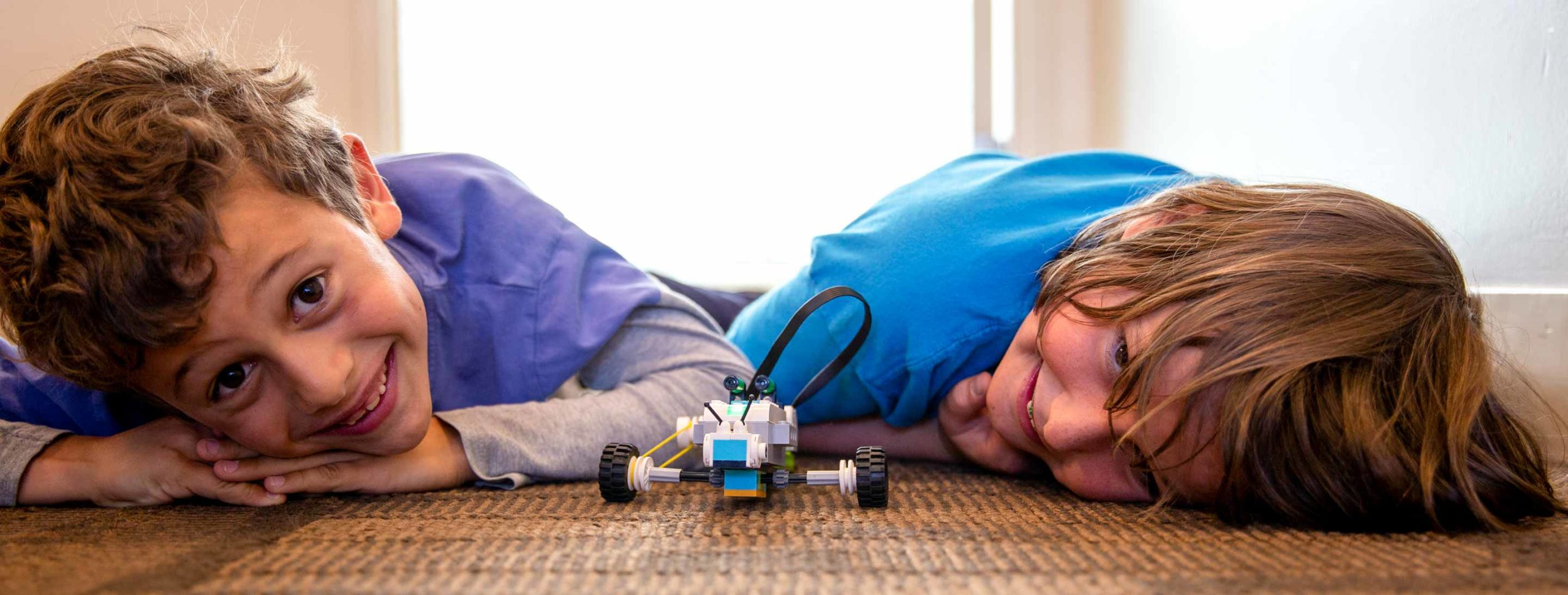Smiling boys lie on floor with Legos