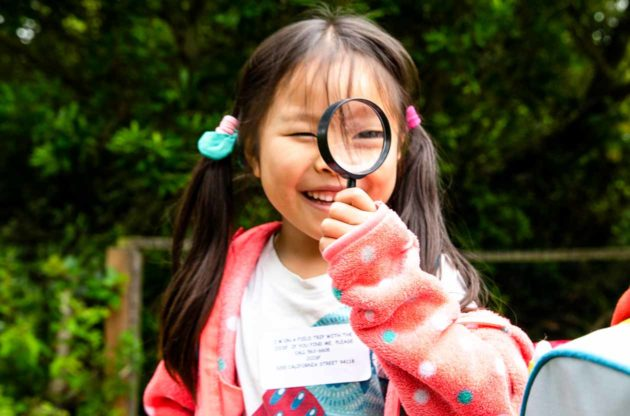 Smiling girl holds magnifying glass in front of face