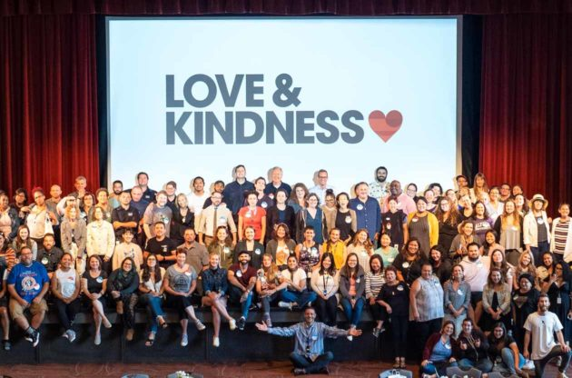 """JCCSF group poses in front of screen reading """"Love & Kindness"""""""