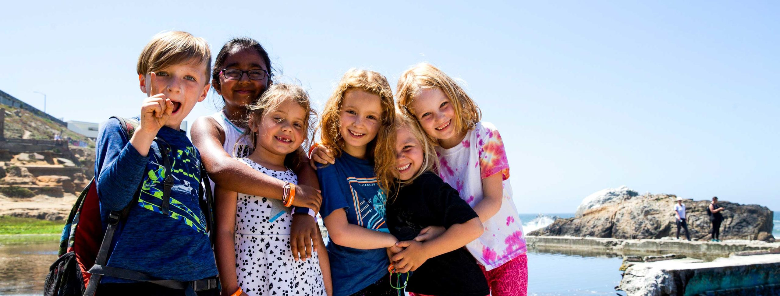 Group of kids hug each other while posing for camera