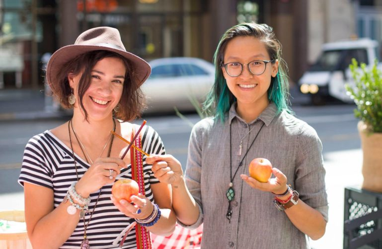 Two people holding apples