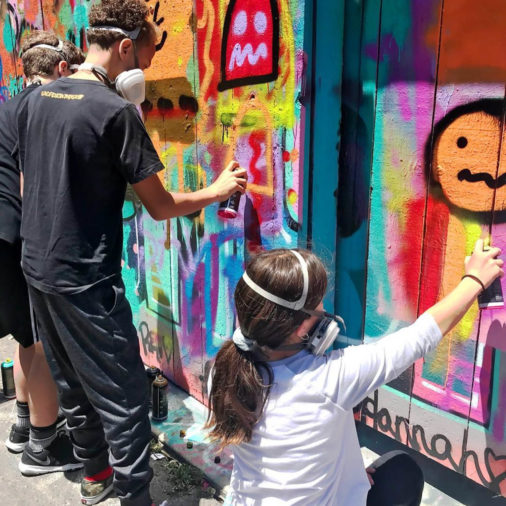 Group of kids spray painting a wall