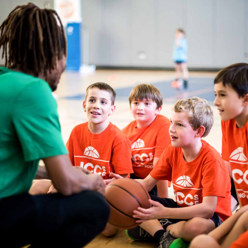 Youth basketball coach chats with kids