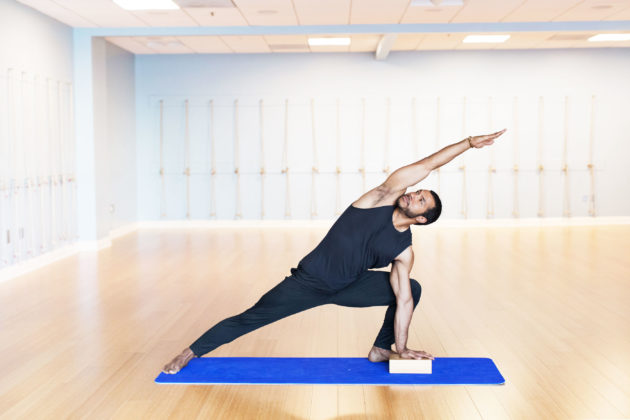 man stretching on yoga mat