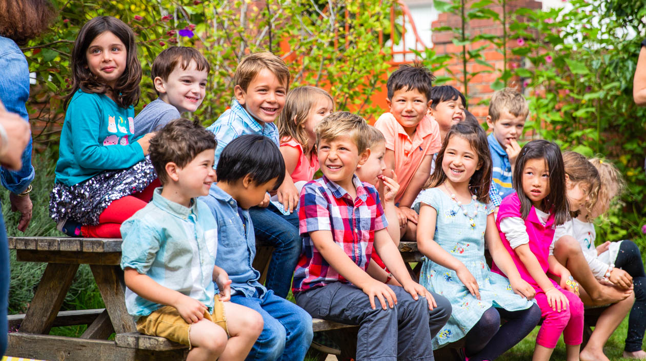 Graduating preschool class sits on picnic table