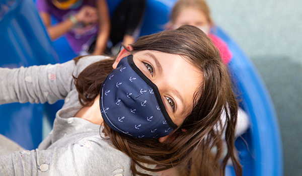 young girl wearing dark blue face mask with white anchors on it