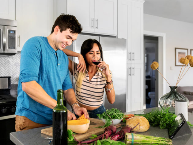 Couple cooking and drinking wine in the kitchen