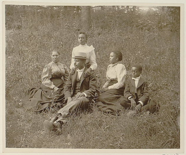 African American family posed for portrait seated on lawn from 1899 or 1900