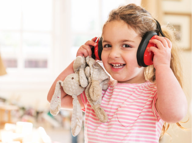 Little girl wearing headphones while holding a stuffed animal