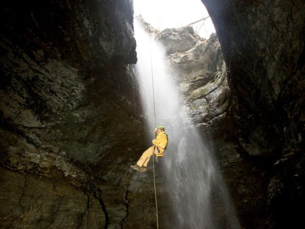 Man hanging from rope in cave
