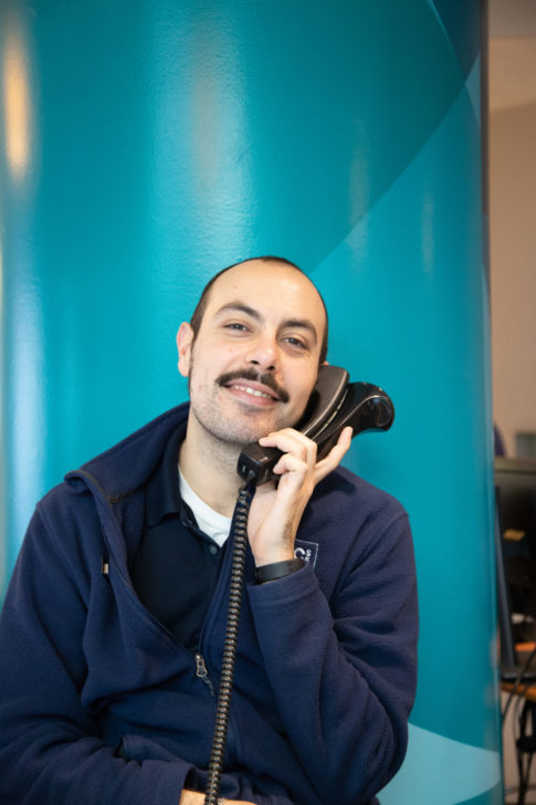 Smiling picture of man with a mustache talking on the phone