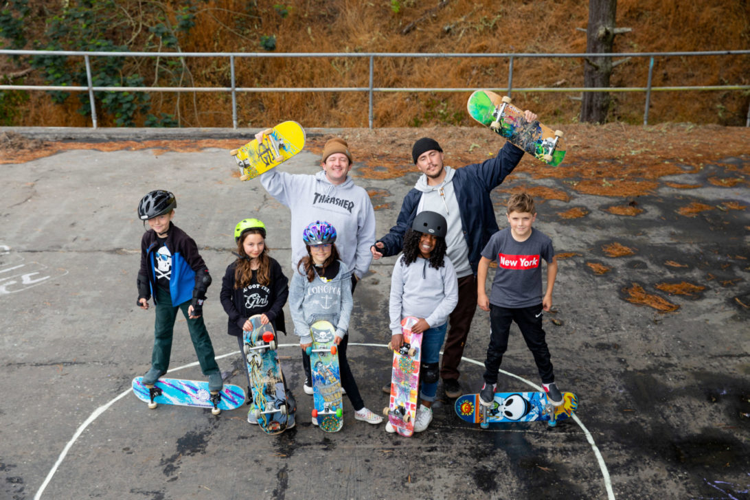 picture of 5 young children with skateboards and 2 instuctors