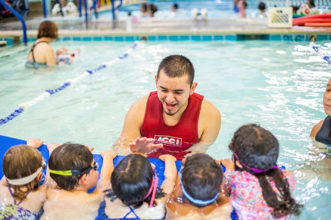 Swim instructor with short hair teaching 4 children