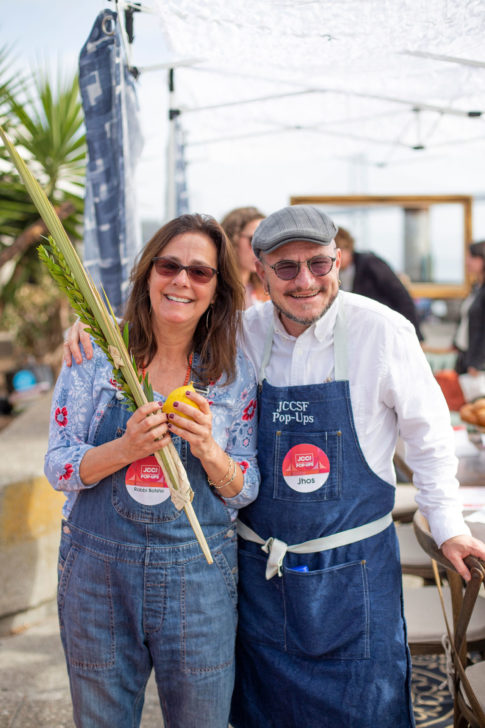 a woman with medium length brown hair and blue overalls carrying a lulav and etrog smiling next to a smiling man in a kangol style hat with a JCCSF apron on.