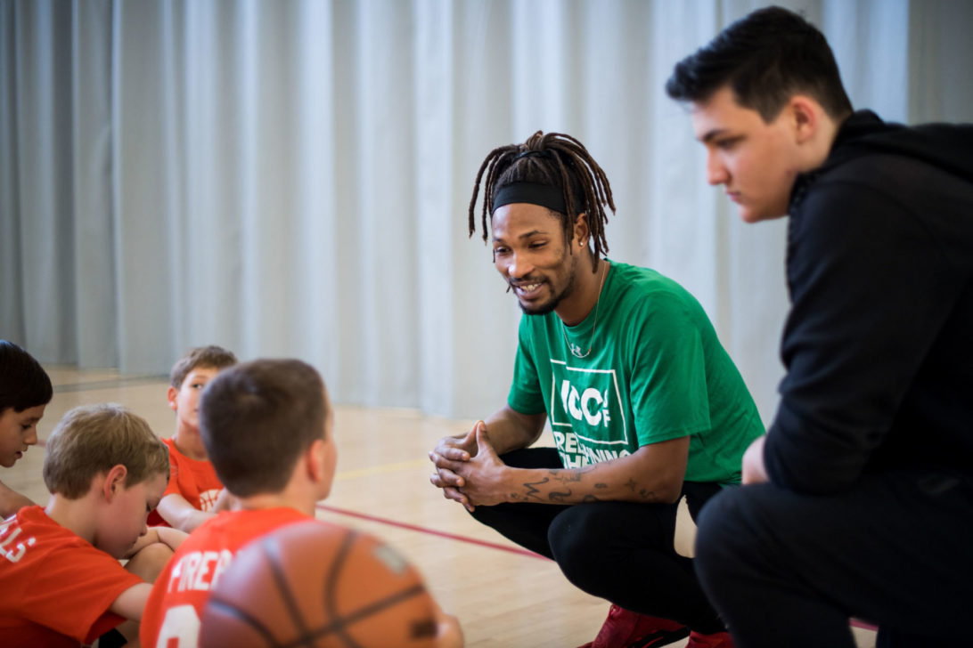 smiling basketball coach with dreads in a green JCCSF shirt speaking to several young basketball players