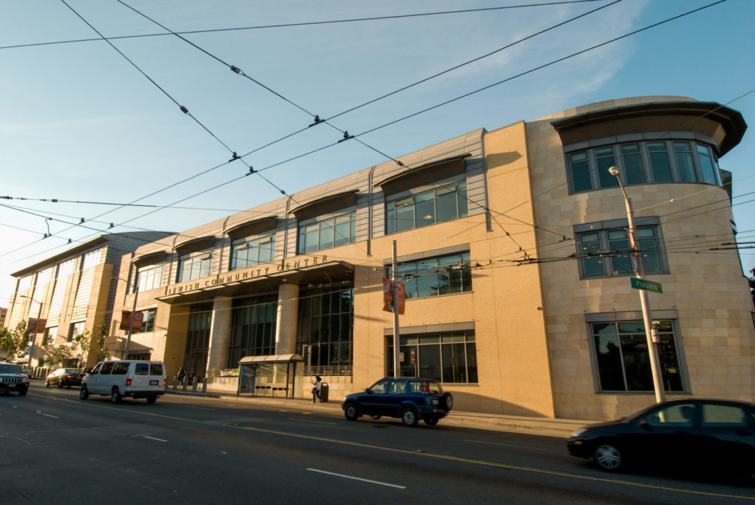 picture of the JCCSF from the outside. It is a large, 3 story building that is beige with many windows