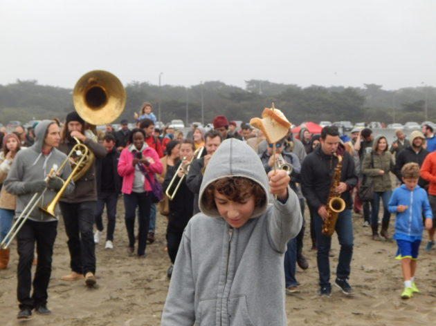 People walking on the beach with instruments