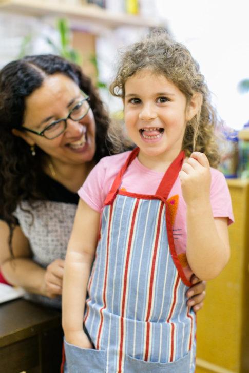 preschool teacher and preschool girl smiling