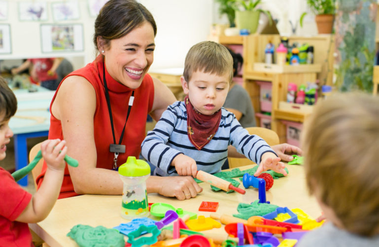 teacher showing preschool boy how to roll dough and smiling at other students
